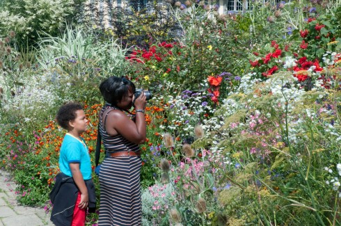 Enthusiastic visitor taking pics of the long border at Great Dixter August 2011